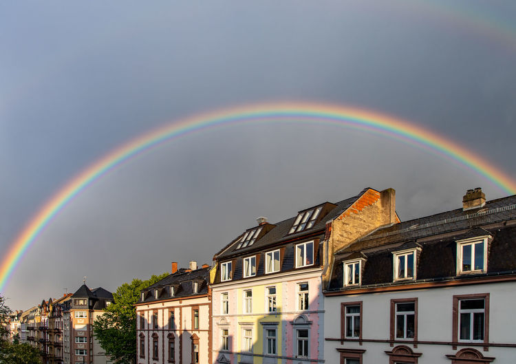 Rainbow over buildings in city against sky