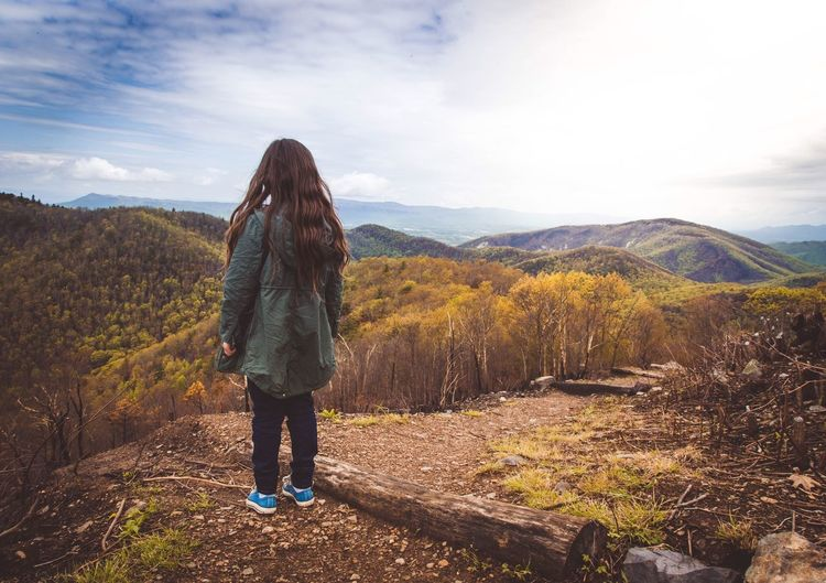 Rear view of girl standing on mountain against sky