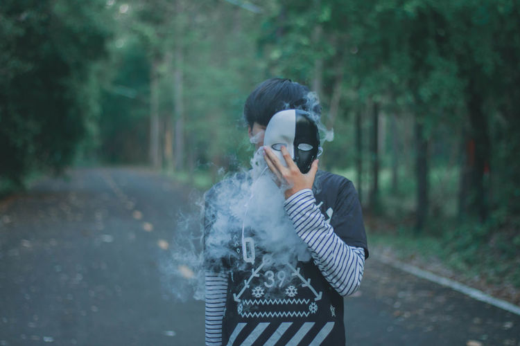 Man holding mask with smoke over face while standing against trees in forest