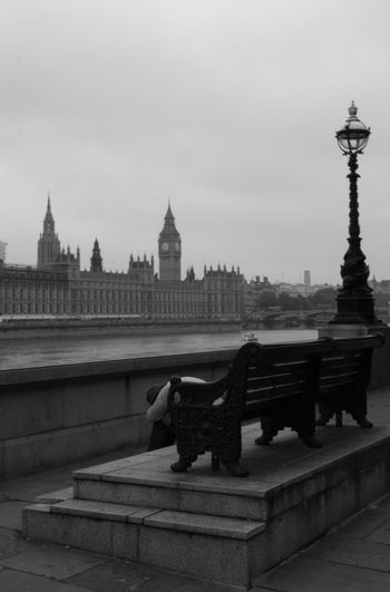 Bench by thames river in city against sky