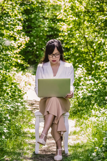 Woman using laptop while sitting on chair by plants