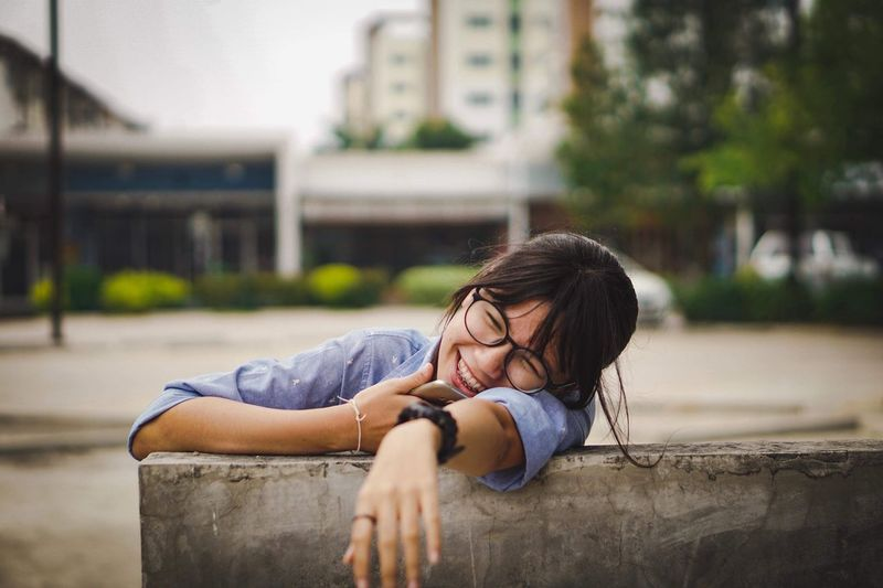Cheerful Teenage Girl Sitting On Bench In City