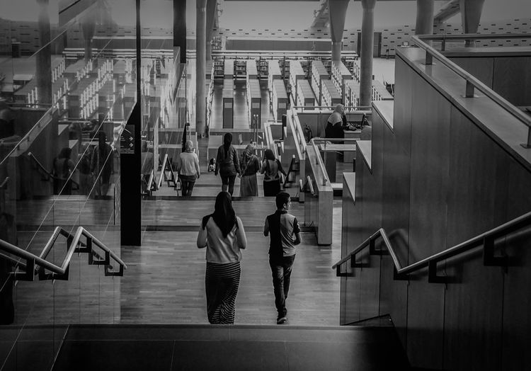 High angle view of people walking on staircase in library