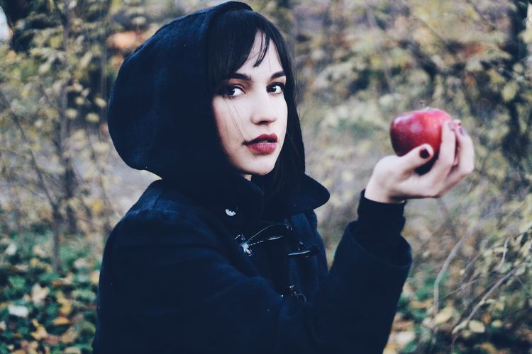 Portrait of young woman holding red apple while standing at park