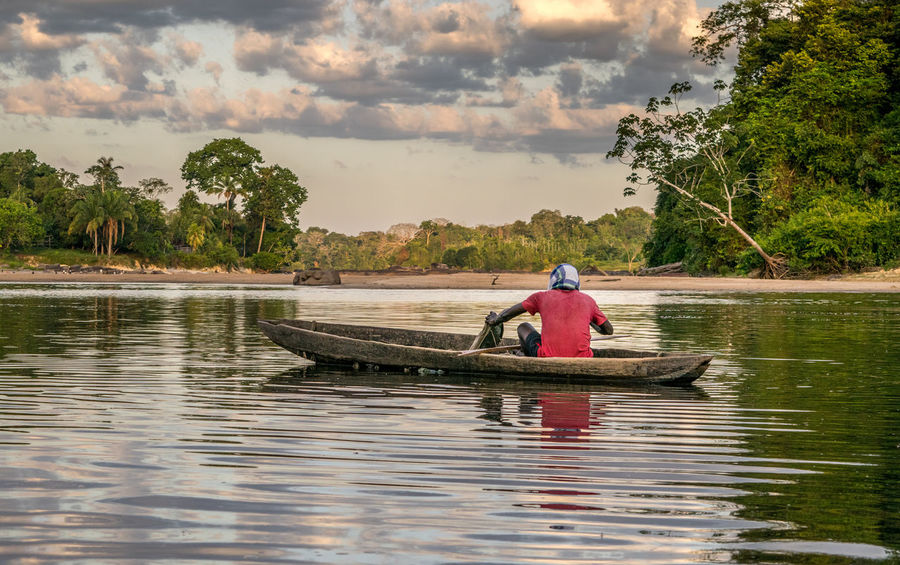 Fisherman in traditional boat Beauty In Nature Boat Cloud - Sky Day Jungle Men Nature Nautical Vessel One Person Outdoors Palm Tree People Rainforest River Sky Suriname Tourism Tranquility Transportation Travel Destinations Tree Vacations Water