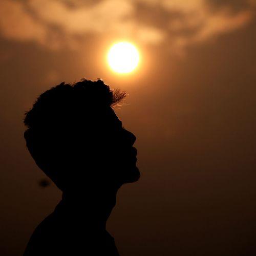 Silhouette Teenage Boy Against Orange Sky
