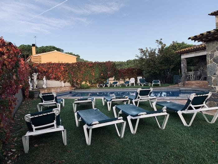 Empty chairs and tables on lawn