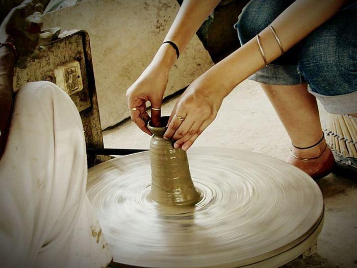 Midsection Of Female Potter Making Pots At Workshop