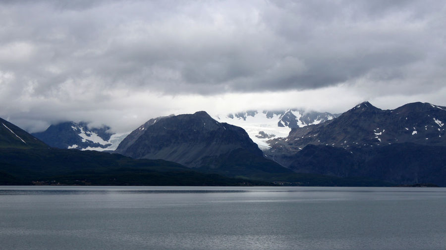 Scenic View Of Mountains And Lake Against Cloudy Sky