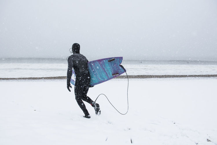 Man with umbrella on sea shore during winter
