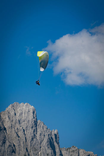 Paraglider Paragliding Adventure Extreme Sports Sport Mid-air Sky Leisure Activity Flying Parachute Low Angle View Cloud - Sky Real People Day Lifestyles One Person Blue Unrecognizable Person Nature Beauty In Nature Exhilaration Freedom Outdoors