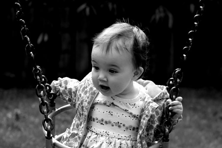 Cute baby girl sitting on swing in playground