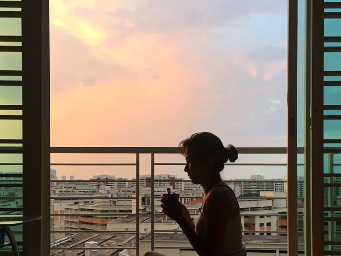 Side view of young woman looking through window at sunset