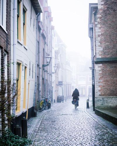 Rear view of man walking on street amidst buildings