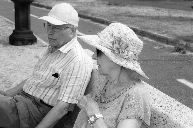Elderly couple sitting on a bench by the lake. black and white photo.