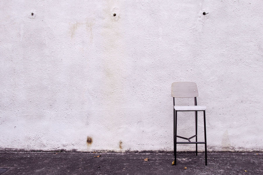 Empty bar chair right in front of white wall. Alone Casual City Emptiness Lifestyle Loneliness Chair No People Rest Seat Simple Single Space Wall White Color