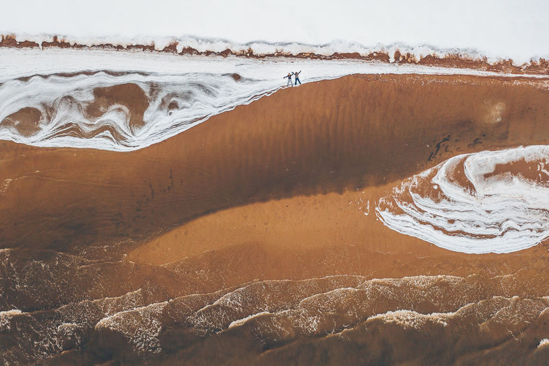 Aerial View Of Friends Lying At Beach During Winter