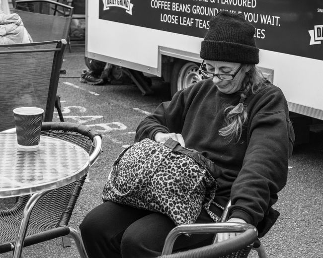 Coffee break while market shopping. Bury St Edmunds, Suffolk Break Time Real People Sitting Clothing One Person Hat Lifestyles Seat Leisure Activity Shopping Casual Clothing Knit Hat Street Streetphotography Street Portrait Black And White Black And White Collection  Black And White Portrait Market Shopping Coffee Time Coffee Break