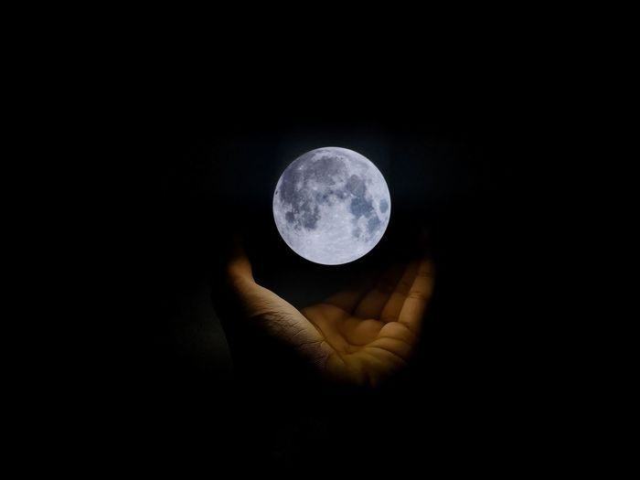 Reflection of person hand holding moon against dark sky