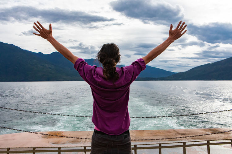 Rear view of woman with arms outstretched standing on mountain against sky