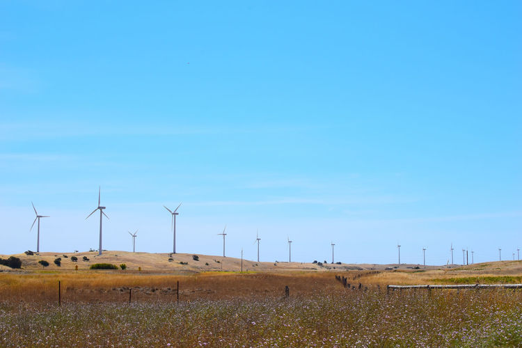 Wind turbines on field against sky