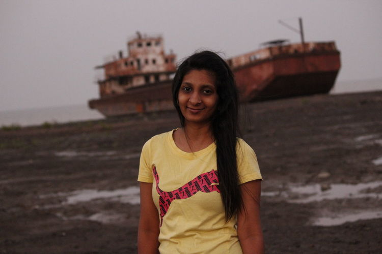 Portrait of young woman standing against old ship at beach