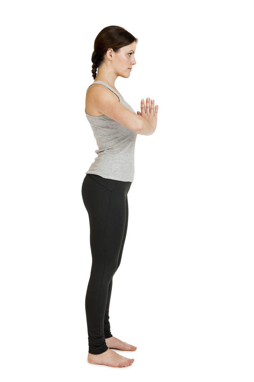 Full Length Side View Of Woman Standing With Hands Clasped Against White Background