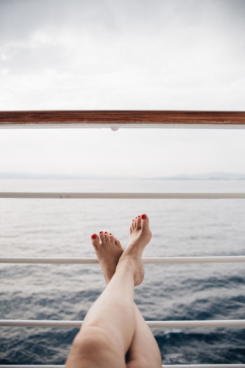 Low section of woman relaxing against sea