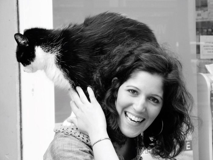 Portrait of happy woman carrying cat on shoulder
