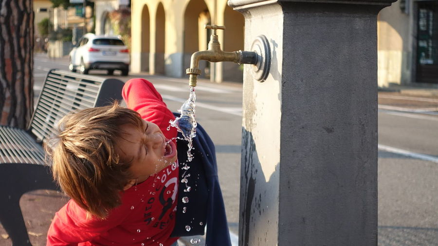 Girl drinking water from faucet on footpath