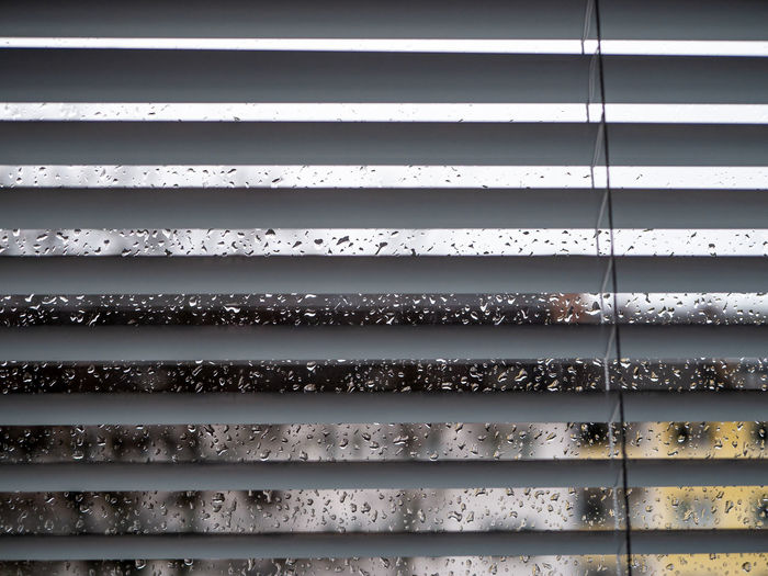 Rainy weather: Wet window with raindrops and grey sky, houses out of focus in background Pattern Full Frame Backgrounds No People Metal Day Security Blinds Architecture Safety Protection Close-up Repetition Built Structure Window Outdoors Textured  Wall - Building Feature Silver Colored Iron - Metal Ceiling Steel