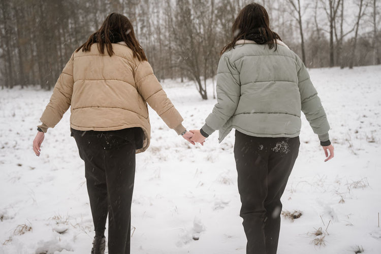 Rear view of young women standing on snow outdoors