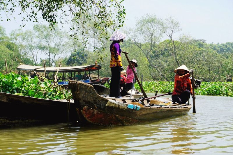 People in boat on water by trees