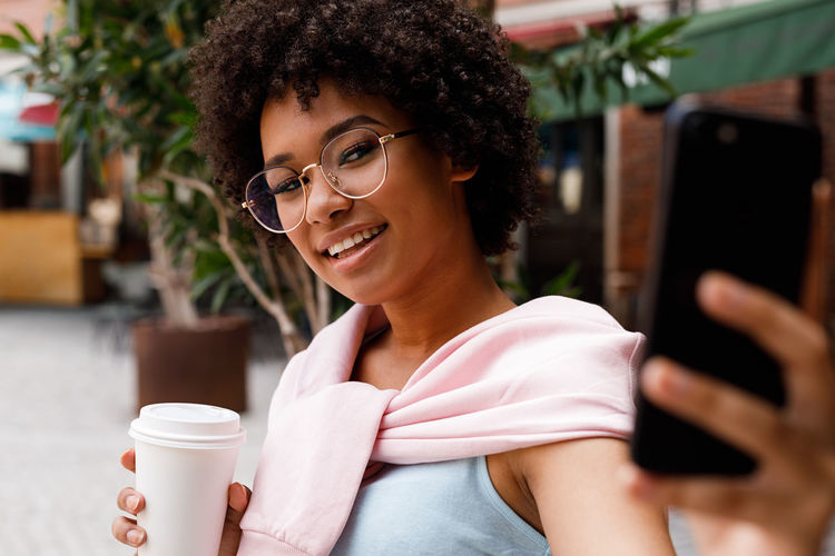 Smiling Young Woman With Afro Hairstyle Taking Selfie