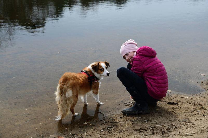 Smiling girl crouching by dog at lakeshore