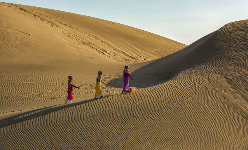 Women carrying containers while walking on sand dunes in desert