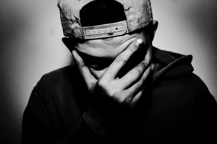 Close-up of young man covering face on gray background