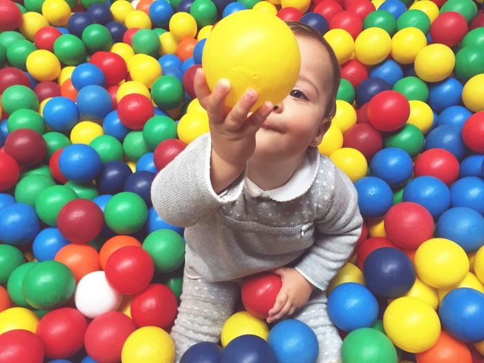 EyeEm Selects Multi Colored Childhood Fun Playing Ball Happiness Enjoyment Balloon Front View Leisure Activity One Person Smiling Indoors  Large Group Of Objects Real People Portrait Day Clown Pool Ball People Baby