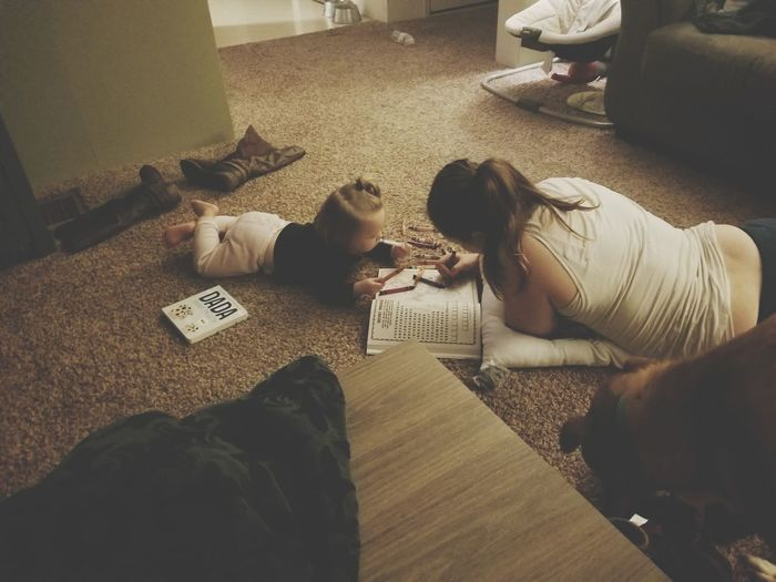 Mother And Daughter Coloring Book While Lying On Floor At Home