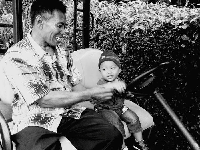 Grandfather And Grandson Sitting In Golf Cart