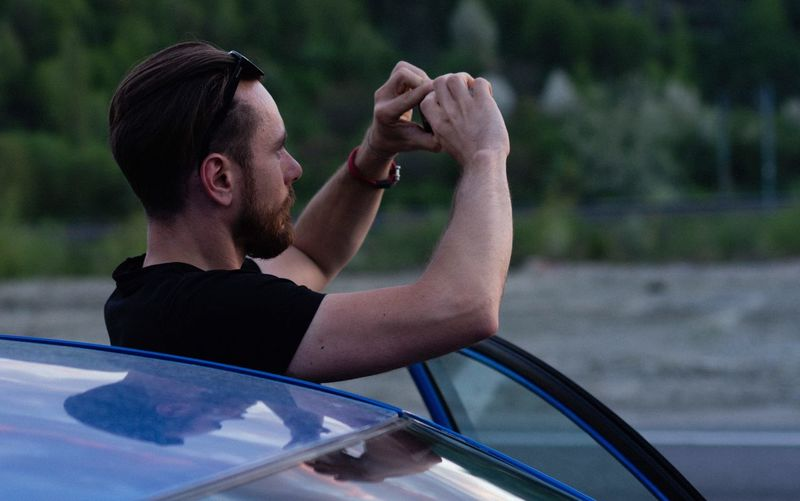 Side view of man photographing by car