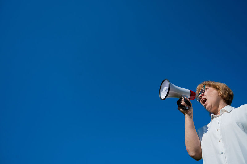Low angle view of woman talking on megaphone against sky