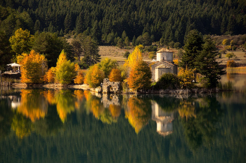 Reflection Of Trees And Buildings On Lake During Autumn