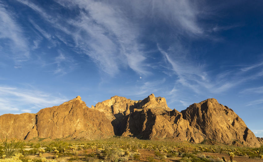 A partial moon rises over the KofA Range in Western Arizona. Sky Rock Rock Formation Cloud - Sky Scenics - Nature Beauty In Nature Tranquil Scene Environment Nature Landscape Tranquility No People Sunlight Mountain Mountain Range Formation Outdoors Arid Climate Eroded Arizona Yuma County Kofa National Wildlife Refuge Moonrise Sunset Force Of Nature