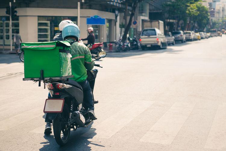 Rear view of delivery person riding motorcycle on road in city
