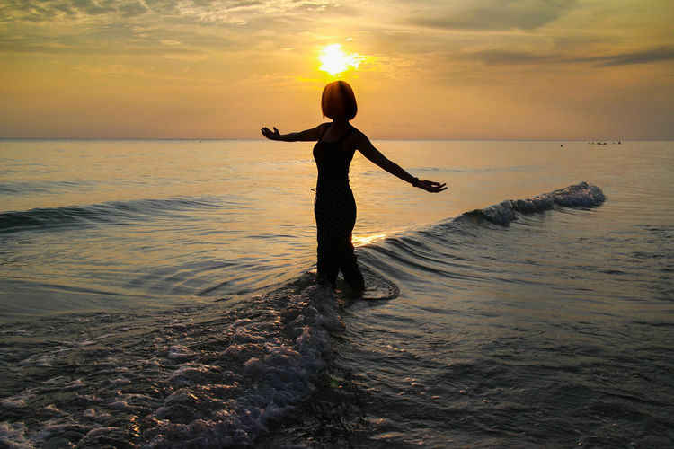 Silhouette woman with arms outstretched standing in sea against orange sky