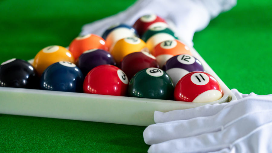 Close-up of hand holding balls on pool table