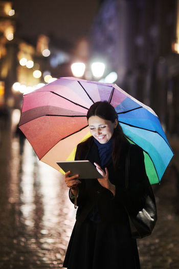 , Touch Pad Brunette Caucasian City Evening Female Girl Moody Multicolored Rain Street Tablet Technology Touch Pad Touchpad Umbrella Vertical Woman Young