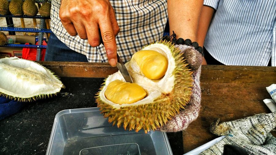 Midsection of man selling durian at market stall