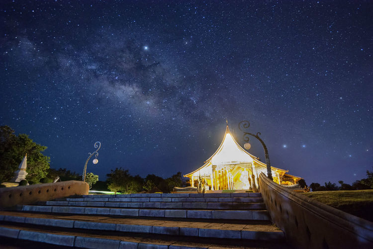Low angle view of illuminated temple against star field at night